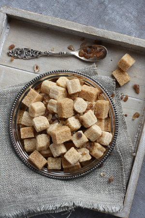 Heap of brown sugar cubes on metal plate on wooden tray photo
