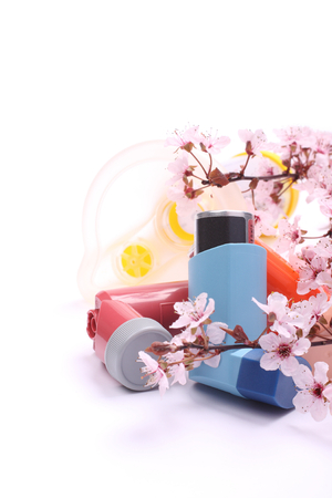 Asthma inhalers with extension tube for children and blossoming tree branches over white Stock Photo