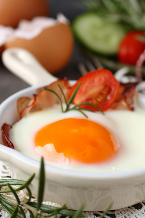 Fried egg with bacon in ceramic pan on wooden background Stock Photo