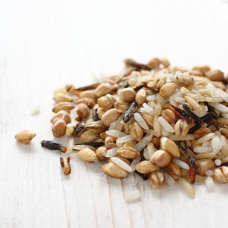 Pileof uncooked multigrain rice on white wooden background