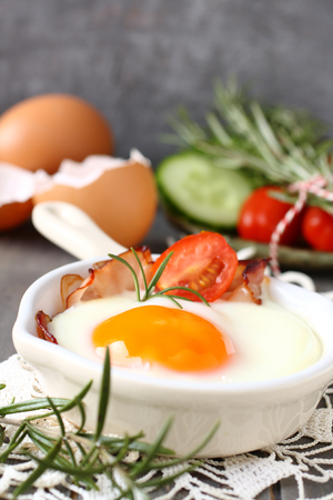 Fried egg with bacon in ceramic pan on wooden background photo