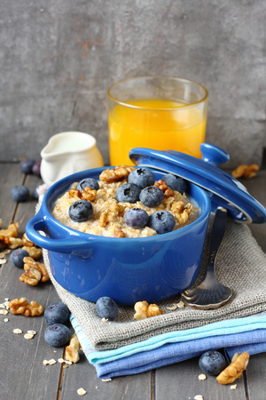 Oatmeal with fresh blueberries over a rustic wooden background photo