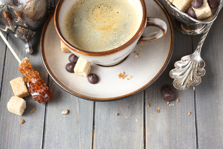 Cup of coffee, sugar cubes and chocolate drops on old wooden background with copy space Stock Photo