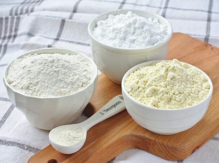 Drie kommen met glutenvrij meel - rijstmeel, gierst bloem en aardappelzetmeel en lepel met xanthaangom Stockfoto