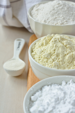Three bowls with gluten free flour - rice flour, millet flour and potato starch and spoon with xanthan gum Standard-Bild