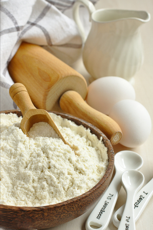 Homemade gluten free flour blend from rice flour, millet flour, potato starch and xanthan gum in wooden bowl met scoop Standard-Bild