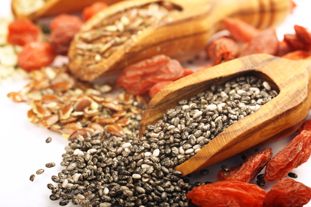 Superfoods in wooden scoops, one of the superfoods (seeds of chia, hemp and flax and Goji berries) photo