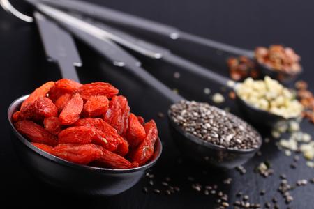 common flax: Goji berries, chia seeds, hemp seeds and broken flax seeds in metal measuring spoons