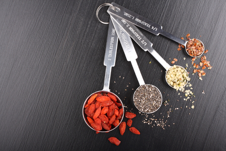 Goji berries, chia seeds, hemp seeds and broken flax seeds in metal measuring spoons