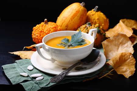 Pumpkin soup in white plate with fresh pumpkins on black background Stock Photo