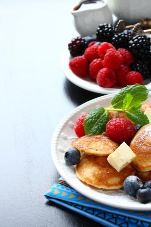 Dutch mini pancakes called poffertjes with berries