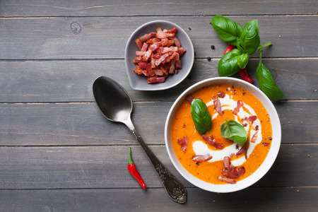 cooking ingredients: Carrot sweet pepper cream soup with bacon Stock Photo