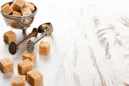 tongs: Brown sugar cubes and metal sugat tongs Stock Photo