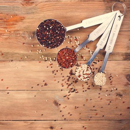 Mezcla de granos de quinua en cucharas de medir de metal Foto de archivo