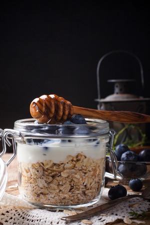 Muesli con el yogur y las bayas azules en frasco de vidrio. Foto de archivo