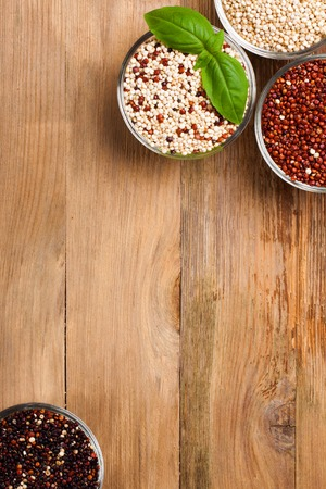 White, red, black and mixed raw quinoa, South American grain, in glass bowls with basil leaves on old rustic wooden background. Top view. Background with copy space. Healthy food concept.