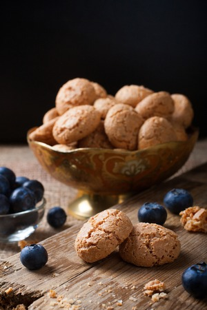 Italian almond cookie amaretti with blueberries on rustic wooden board, selective focus, law key. Stock Photo