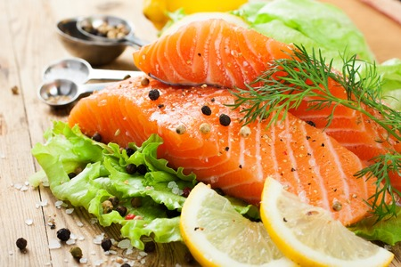 Delicious salmon fillet, rich in omega 3 oil, aromatic spices and lemon on fresh lettuce leaves on rustic wooden background. Healthy food, diet and cooking concept.