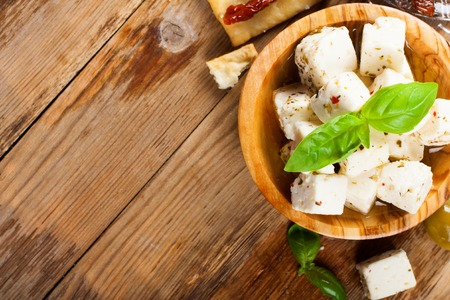 vegan: Cubes of feta cheese in olive wood bowl and green and black olives on rustic wooden background.  Selective focus. Food background with copy space. Stock Photo