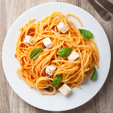 Spaghetti with tomato sauce, feta cheese and basil leaves on white plate on wooden background. Italian helthy food background. View from above.