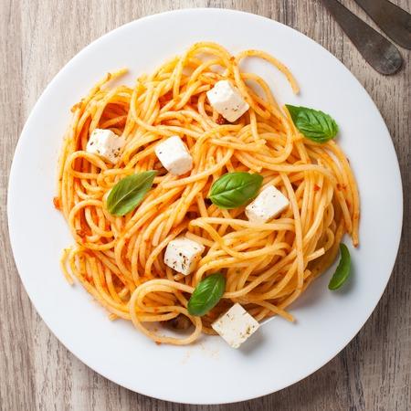 italienisches essen: Spaghetti mit Tomatensauce, Feta-Käse und Basilikum Blätter auf weißem Teller auf Holzuntergrund. Italienisch helthy Lebensmittel Hintergrund. Ansicht von oben.