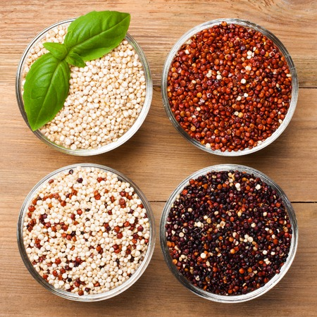 White, red, black and mixed raw quinoa, South American grain, in glass bowls on old rustic wooden background.  Stock Photo