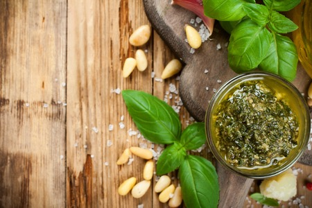 bawl: Homemade green pesto in glass bawl on a rustic wooden cutting board and fresh ingredients.