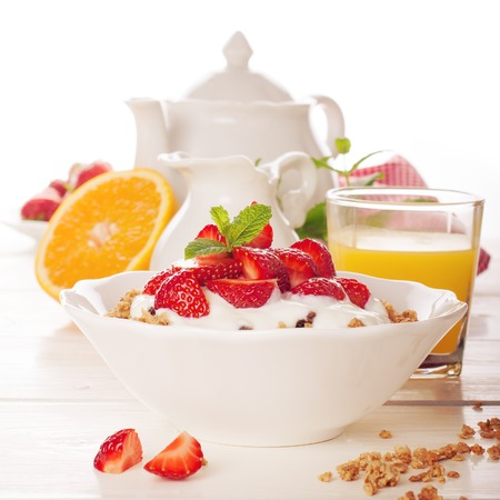 Yogurt with homemade granola and fresh strawberries in white ceramic bowl on white wooden background. Selective focus. Toned, soft light.