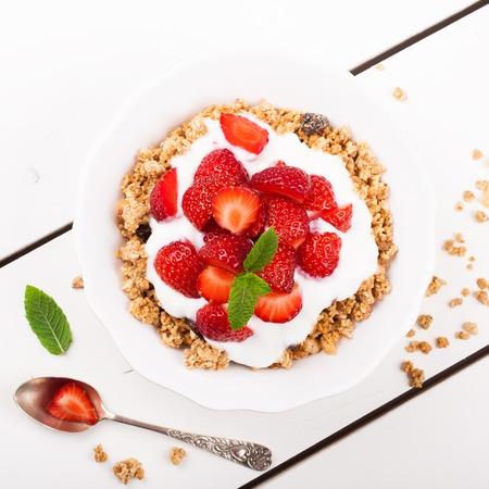 yogur: Fresas frescas, yogur y granola casera para el desayuno saludable en el fondo blanco, foco selectivo. Vista superior. Foto de archivo