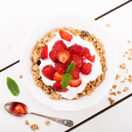 dessert: Fresh strawberries , yogurt and homemade granola for healthy breakfast on white background, selective focus. Top view.