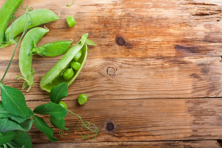 healthy grains: Fresh green peas on old wooden background. Selective focus. Healthy food concept witj copy space