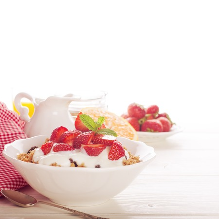 Yogurt with homemade granola or muesli and fresh strawberries for healthy morning breakfast, selective focus, over white. Healthy food background with copy space for text. Toned, soft light.