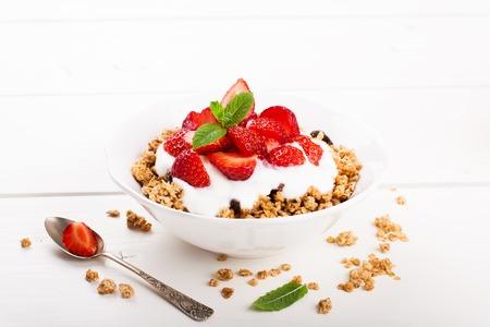 prima colazione: Fragole fresche, yogurt e muesli fatti in casa per la prima colazione sana su sfondo bianco, messa a fuoco selettiva. Archivio Fotografico