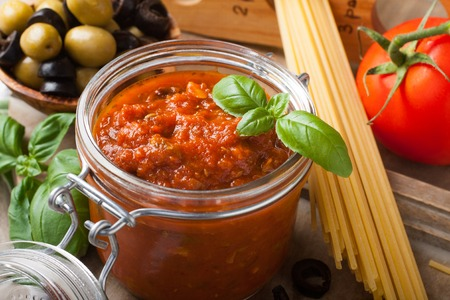 Glass jar with homemade classic spicy tomato pasta or pizza sauce with olives and basil. Italian healthy food background.