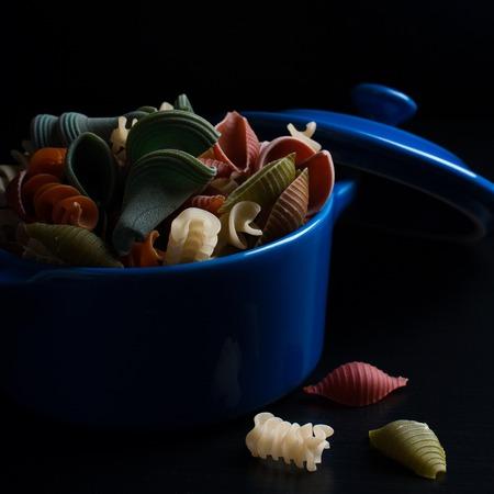 Different types of wholegrain spelt pasta in blue ceramic pot on black background. Selective focus. Stock Photo