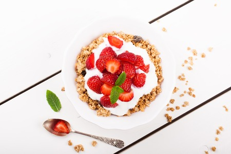 Yogurt with homemade granola or muesli and fresh strawberries for healthy morning breakfast, selective focus, over white. Healthy food background. Top view.