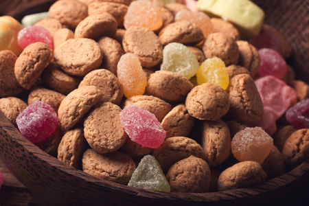strooigoed: Gingerbread nuts or pepernoten and colorful candies in wooden bowl, typical Dutch candy for a dutch holiday Sinterklaas on the fifth of december.