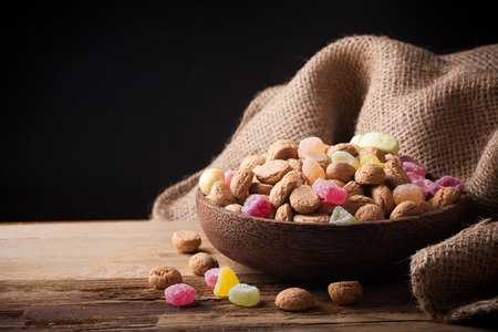 strooigoed: Gingerbread nuts or pepernoten and colorful candies in wooden bowl, typical Dutch candy for a dutch holiday Sinterklaas on the fifth of december. With copy space.