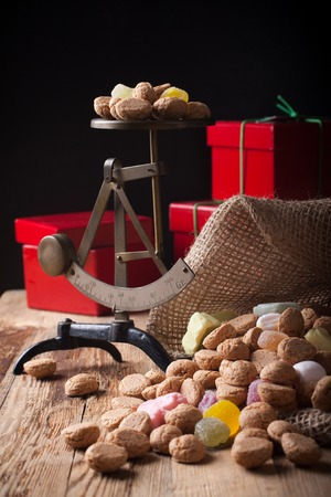 zwarte: Typical dutch sweets for Sinterklaas - pepernoten ginger nuts and colorful candies with gifts and small scales in the background. Selective focus. Stock Photo