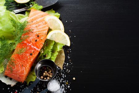 lechuga: Delicioso filete de salmón, rico en ácidos grasos omega 3 de aceite, especias aromáticas y limón en hojas de lechuga fresca sobre fondo negro. La comida sana, la dieta y el fondo de cocción, con copia espacio. Foto de archivo