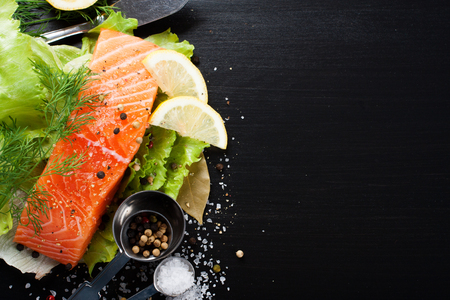 lettuce: Delicious salmon fillet, rich in omega 3 oil, aromatic spices and lemon on fresh lettuce leaves on black background. Healthy food, diet and cooking background with copy space.