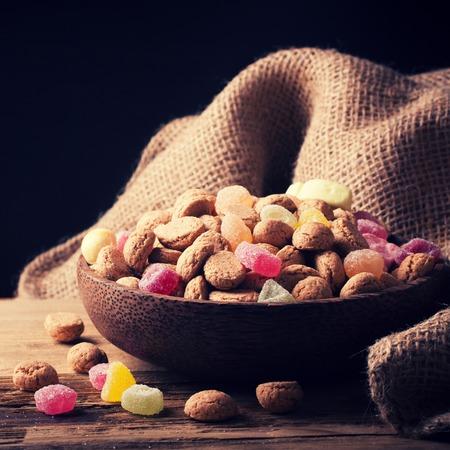 Houten kom met typische Nederlandse snoepjes voor Sinterklaas - pepernoten pepernoten en kleurrijke snoepjes. Selectieve aandacht. Gestemde foto.