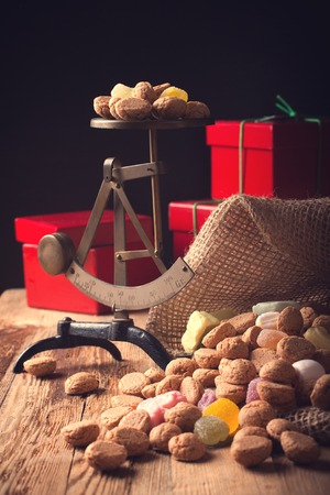 strooigoed: Jute bag with typical dutch sweets for Sinterklaas - pepernoten ginger nuts and colorful candies with gifts and small scales in the background. Selective focus. Toned photo.