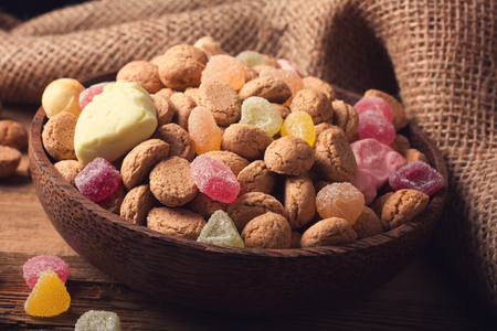 speculaas: Gingerbread nuts or pepernoten and colorful candies in wooden bowl, typical Dutch candy for a dutch holiday Sinterklaas on the fifth of december. Toned photo. Stock Photo