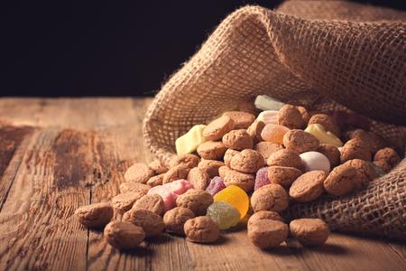 Jute zak met typische Nederlandse snoepjes voor Sinterklaas - pepernoten pepernoten en kleurrijke snoepjes. Selectieve aandacht. Gestemde foto. Stockfoto