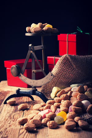 zwarte: Typical dutch sweets for Sinterklaas - pepernoten ginger nuts and colorful candies with gifts and small scales in the background. Selective focus. Toned photo. Stock Photo