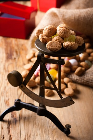strooigoed: Small scales with pepernoten ginger nuts - traditional dutch sweets for Sinterklaas with gifts in the background. Selective focus. Stock Photo