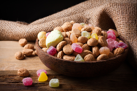 speculaas: Gingerbread nuts or pepernoten and colorful candies in wooden bowl, typical Dutch candy for a dutch holiday Sinterklaas on the fifth of december.