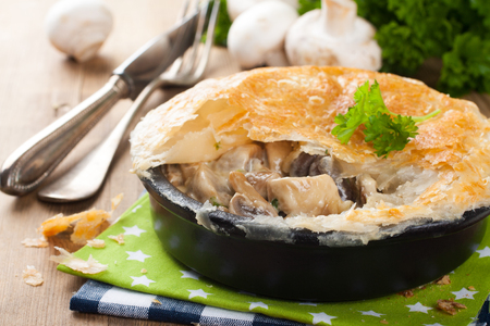 Stewed mushrooms with cream and parsley under puff pastry. Healthy food concept.
