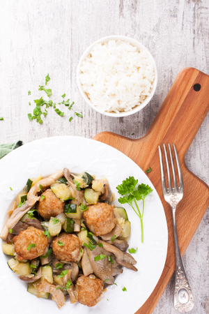 cutting bord: Chicken meatballs with oyster mushrooms, zucchini and rice on white plate and wooden cutting board.  Healthy food concept.  Top view.
